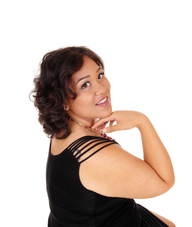 mixed raced: A beautiful young mixed raced woman in a black dress with her hand under her chin, isolated for white background.