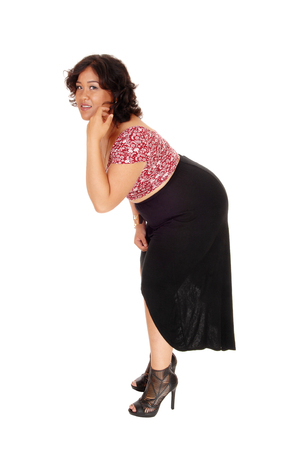 plus sized: A plus sized young woman standing isolated for white background in a black skirt, bending forward.
