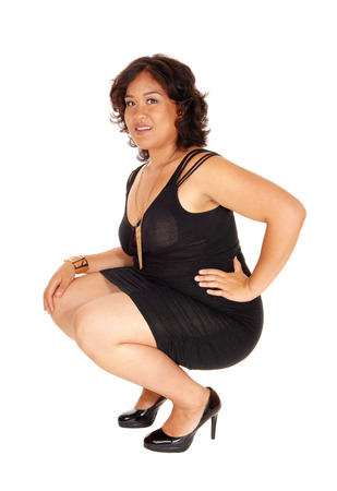 mixed raced: A young mixed raced woman in heels and black dress crouching on the  floor, isolated for white background.