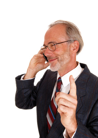 business for the middle: A middle age smiling business man talking on his cell phone, lifting up his finger, telling wait, isolated for white background.