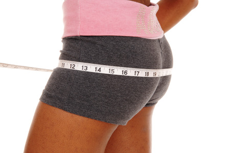 A young african american woman in a closeup image of her bottom, measuring her bum, isolated for white background.