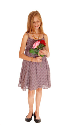 girl in burgundy dress: A pretty young girl in a burgundy dress holding her two roses, smiling, isolated for white background.