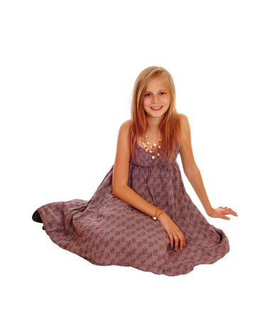 girl in burgundy dress: A gorgeous little girl in a burgundy dress sitting smiling on the floor, isolated for white background.