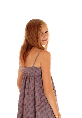 girl in burgundy dress: A lovely young blond girl standing isolated for white background in a burgundy dress, looking over her shoulder. Stock Photo