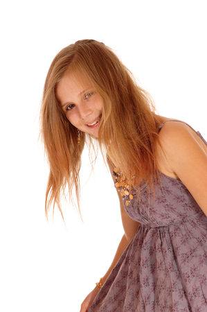 girl in burgundy dress: A smiling lovely little girl in a burgundy dress bending down and her blond hair over her face, isolated for white background.