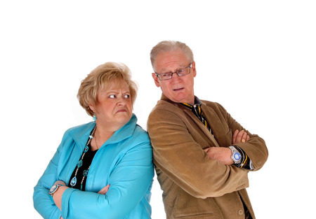 middle age couple: A middle age couple standing back to back are very angry at each other, isolated for white background. Stock Photo