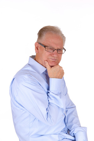 middle: A middle age man in a blue shirt with his hand on his chin, thinking  hard, isolated for white background. Stock Photo