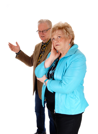 middle age couple: A middle age couple, angry at each other, standing isolated for white background, the man behind his wife.