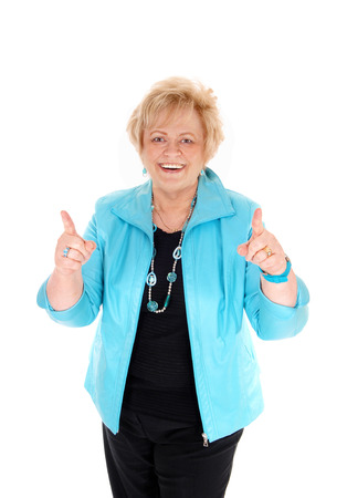 woman middle age: A smiling happy middle age woman in a blue jacket pointing up with her finger, isolated for white background.