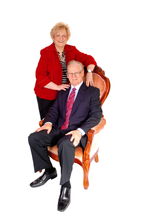 middle age couple: A lovely middle age couple, the man sitting in a armchair and the wife standing behind, formal dressed, isolated for white background.