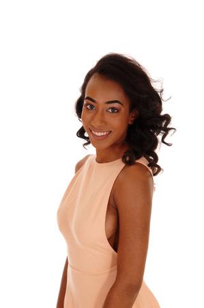 chicas sonriendo: Una hermosa mujer africana Amerikan en un vestido beige con largo cabello negro rizado, aislado de fondo blanco.