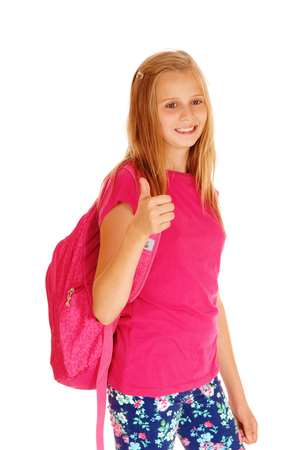 whitebackground: A lovely slim young girl with her backpack on her back standing for white background, smiling and ready to go to school. Stock Photo