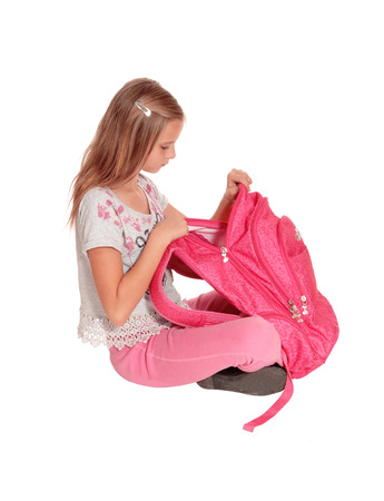A beautiful young girl opening her pink backpack, looking into it and is surprised what she find, isolated for white background. Imagens