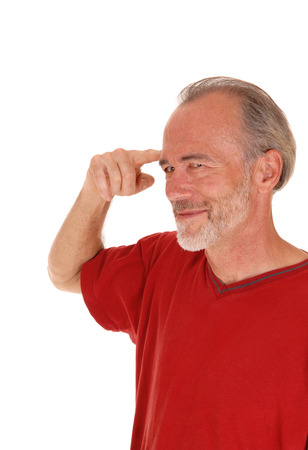 men standing: A closeup image of a middle age man pointing with his finger at his forehead smiling, isolated for white background.