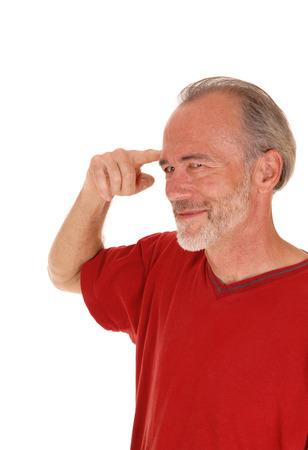 hombres maduros: Un primer imagen de un hombre de mediana edad que apunta con el dedo a la frente sonriendo, aislado de fondo blanco.