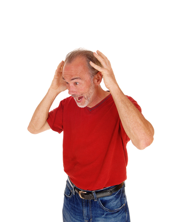 mature men: A older man in a red t-shirt and jeans standing with his hands on his head screaming, isolated for white background.