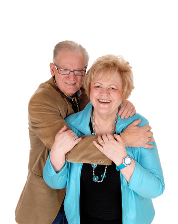 wife: A lovely older couple embracing each other, the man standing behind his wife, hugging, isolated for white background.