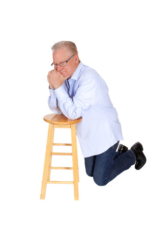 man kneeling: A handsome older man kneeling on a chair and praying, in a blue shirt and jeans, isolated for white background. Stock Photo