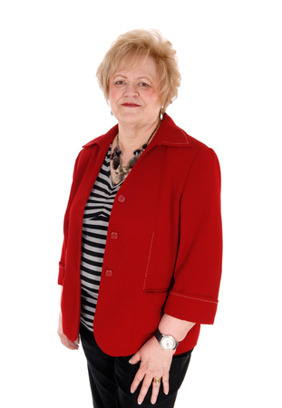 black pants: A lovely older blond woman in a red jacket and black pants standing isolated for white background.