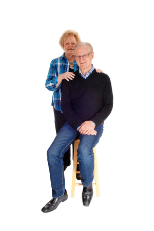 standing together: A senior couple standing isolated for white background, the man sitting on a chair the wife standing behind.