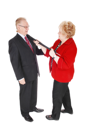 jacked: A senior couple he in a suit and she in a red jacked holding the handle of a umbrella around the mans neck, isolated for white background.