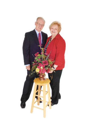 jacked: A nice senior couple in a suit and she in a red jacked standing with some flowers, isolated for white background.