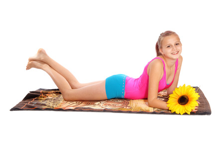 A smiling lovely young girl laying on a towel isolated for white background with a yellow sunflower.