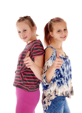 thumps up: Two young girls standing back to back with there thumps up, smiling, isolated for white background. Stock Photo