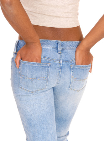 tan woman: A closeup picture of the midsection of a African American woman standing in jeans with her hands in the back pocket, isolated for white background.