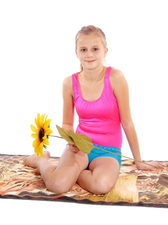 A lovely young girl sitting on a towel isolated for white background with a yellow sunflower. Stock Photo