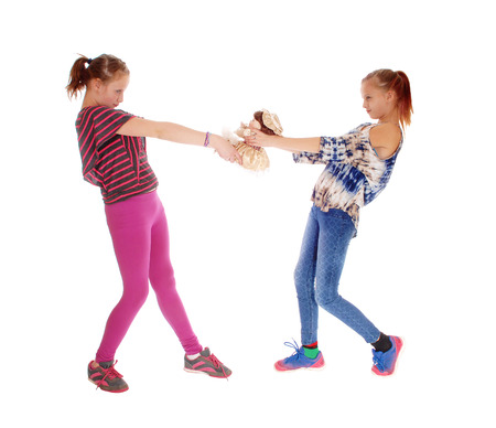 sibling rivalry: Two sisters in pink and blue tights standing and fighting for a dolly, isolated for white background.