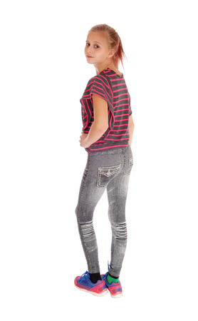 A lovely blond girl in gray jeans and blond hair standing from the back, isolated for white background. Stock Photo