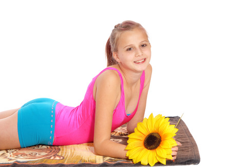 A smiling lovely young girl laying on her stomach on a towel isolated for  white background, with a yellow sunflower.