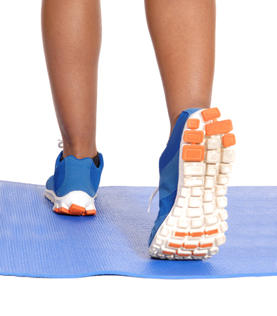 A closeup image of the sneakers and legs of a runner on a blue yoga mat isolated for white background.