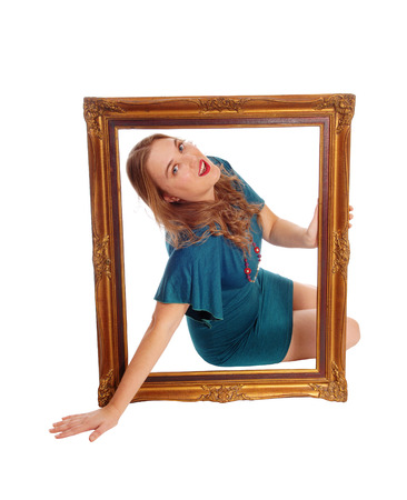 big picture: A young blond woman sitting on the floor holding a big picture frame and looking trough, isolated for white background.