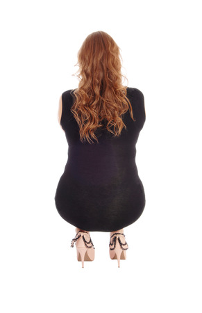 A blond woman in a black dress crouching from the back in high heels, isolated for white background. Stock Photo