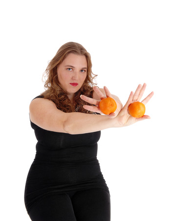 black sweater: A young blond woman in black sweater and tights holding two oranges in her outstretched arms, isolated for white background.