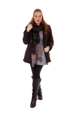 winter woman: A lovely blond young woman standing in a winter jacket and boots with a big scarf, isolated for white background.