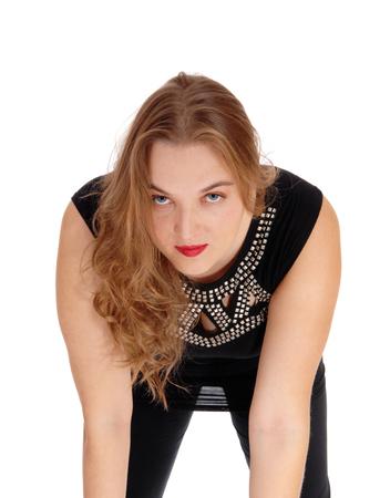 niñas bonitas: Una joven mujer rubia en vestido negro en primer plano se dobla hacia adelante mirando a la cámara, aislado para el fondo blanco.