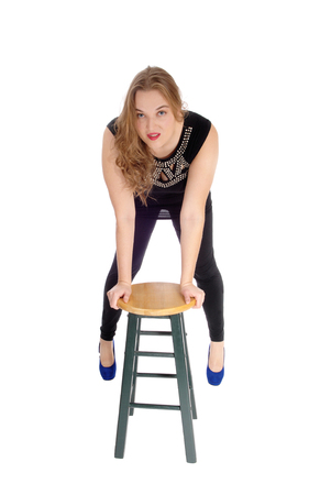 bending forward: A blond young woman in black tights standing bending forward on a chair looking into the camera, isolated for white background.