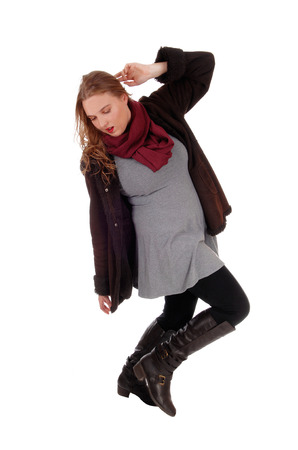 seasonable: A beautiful young woman dancing in a winter coat and black long boots and burgundy scarf, isolated for white background.