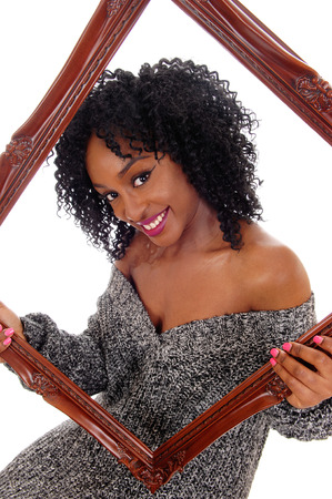 sitting pretty: A beautiful smiling African American women holding a picture frame and looking trough, in gray sweater, isolated for white background. Stock Photo