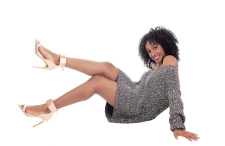 Una hermosa joven afroamericana sentada en el suelo con un suéter gris, sonriendo con el pelo negro rizado, aislado para el fondo blanco. Foto de archivo - 52123880