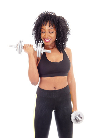 girl working out: A beautiful African American girl working out with two dumbbells in exercise outfit, isolated for white background, and smiling. Stock Photo