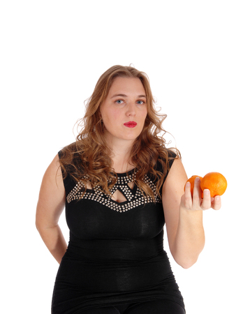 whitebackground: A lovely young woman in an black dress standing isolated for white background holding two oranges.