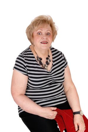 a situation alone: A very surprised looking senior woman sitting on a chair with big eyes, isolated for white background.