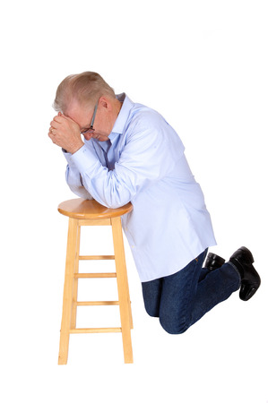 folded hands: A serious senior kneeling on a chair praying with folded hands in a blue shirt and jeans, isolated for white background. Stock Photo