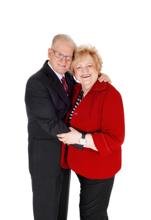 the seventies: A seventies year old couple standing isolated for white background, hugging each other in a suit and red jacket, isolated for white background. Stock Photo