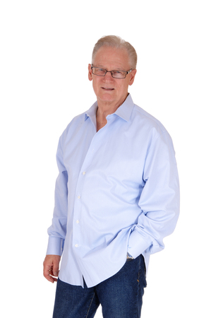 A good looking senior man with glasses standing in a blue shirt with onehand in his jeans pocked, isolated for white background. Archivio Fotografico