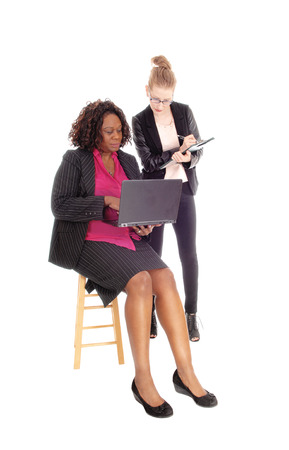 sitting pretty: A Caucasian and African American woman working with a laptop and clipboard in business suit, isolated for white background.